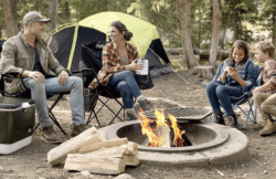 mother, father, and two kids sitting around a campfire with Coleman Camping Equipment