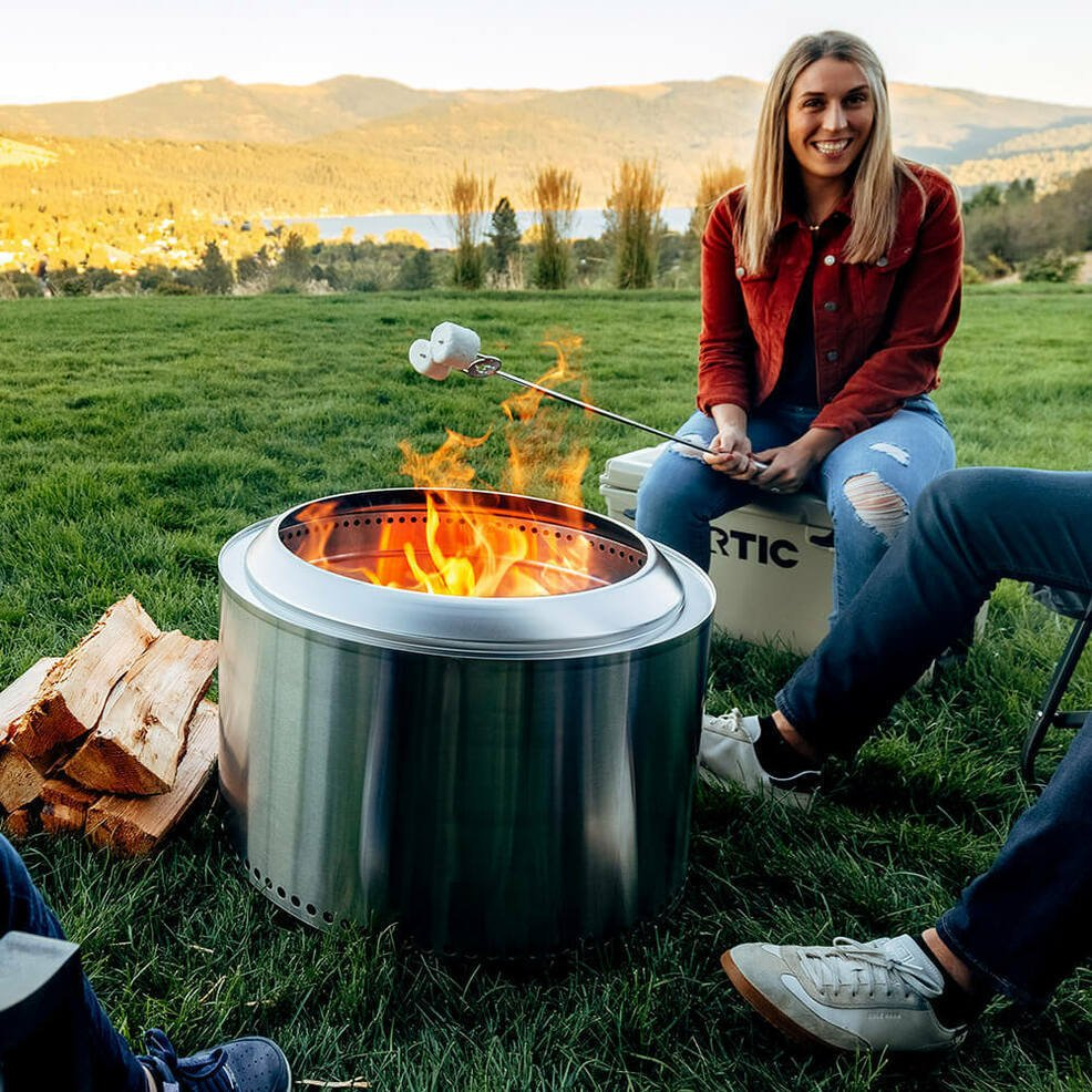 girl outside grilling marshmallows on solo stove