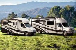 Picture of 2 different RVs parked on green grass with trees and mountains in the background.