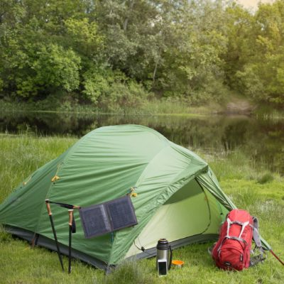 Image of tent set up in green grass, near water, with backpack in front.