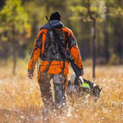Man walking in tall dead grass in fall - with hunting gear.