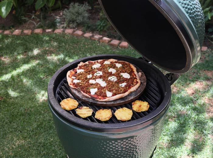 A Big Green Egg with a pizza stone