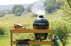 Image of a Big Green Egg in it's grill table smoking away with a lovely natural background.