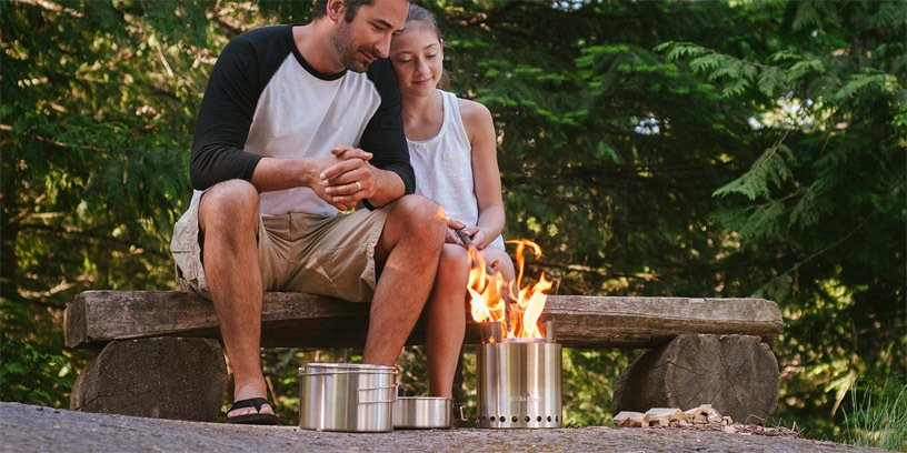 father and daughter sitting next to a small solo stove