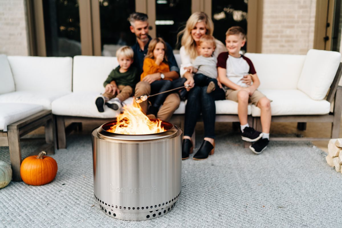 family sitting on patio near solo stove
