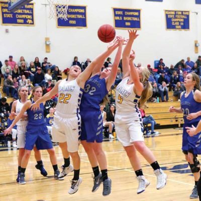 Caroline Wisroth (#22) and Megan Nieslanik (#5) vie for the ball with Tiffany Hildebrandt (#32) while Jaci McDiffett (#23) guards Kendall Bernot (#33) in the 41-40 loss to the Moffat County Bulldogs on Jan. 26. Photo by Sue Rollyson