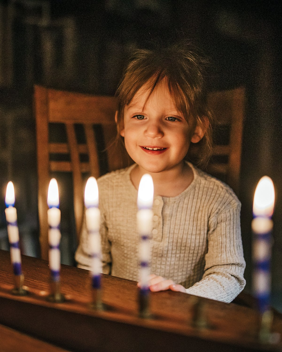 Adee Briggs, 3, learns about Chanukah and lights the Menorah candles for the first time. Photo by Sue Rollyson