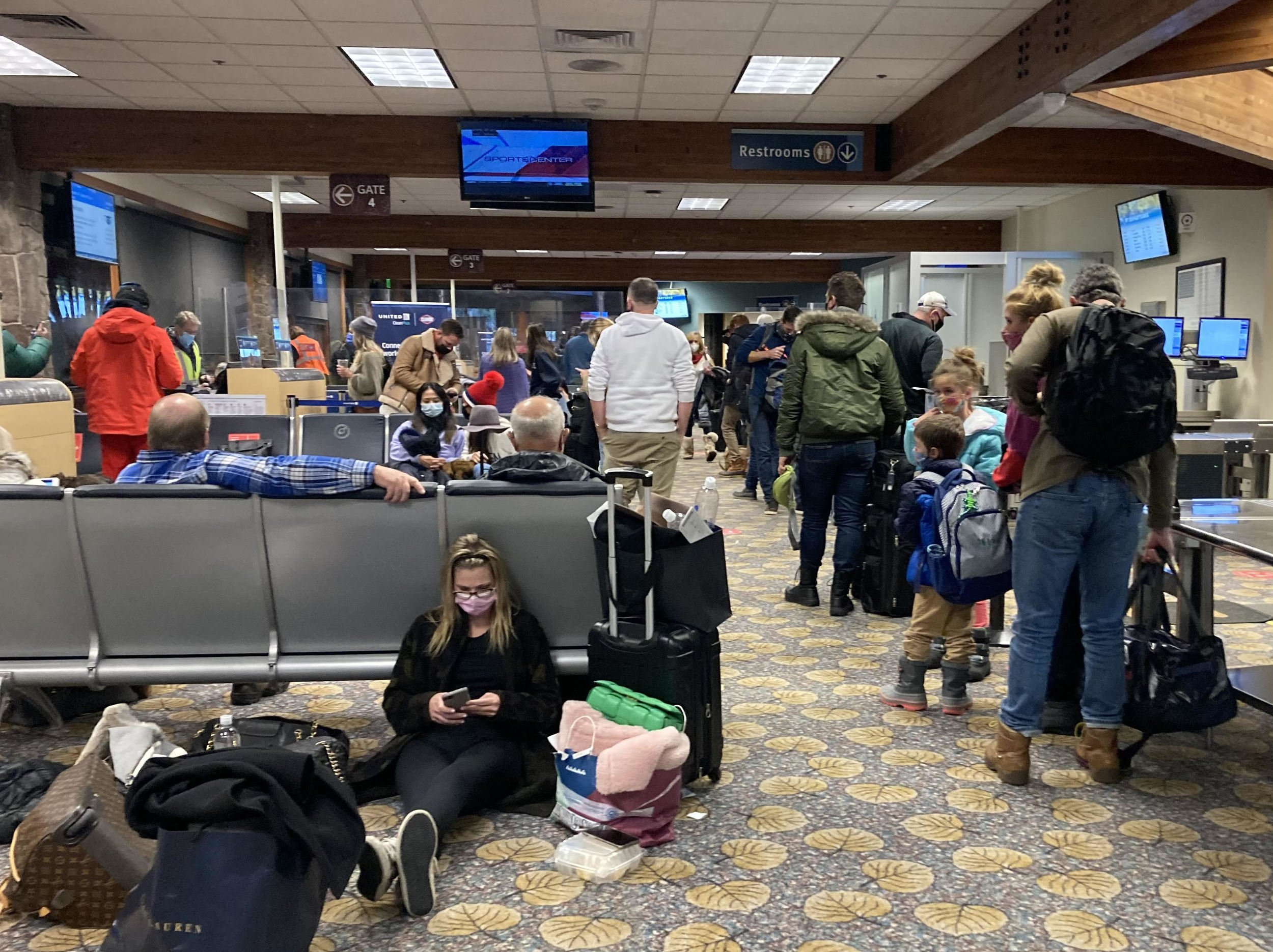 People continue to travel over the holidays through the Aspen Airport, though they had ahard time adhering to the intermittent advisory to keep their distance from one another. Photo by James Steindler