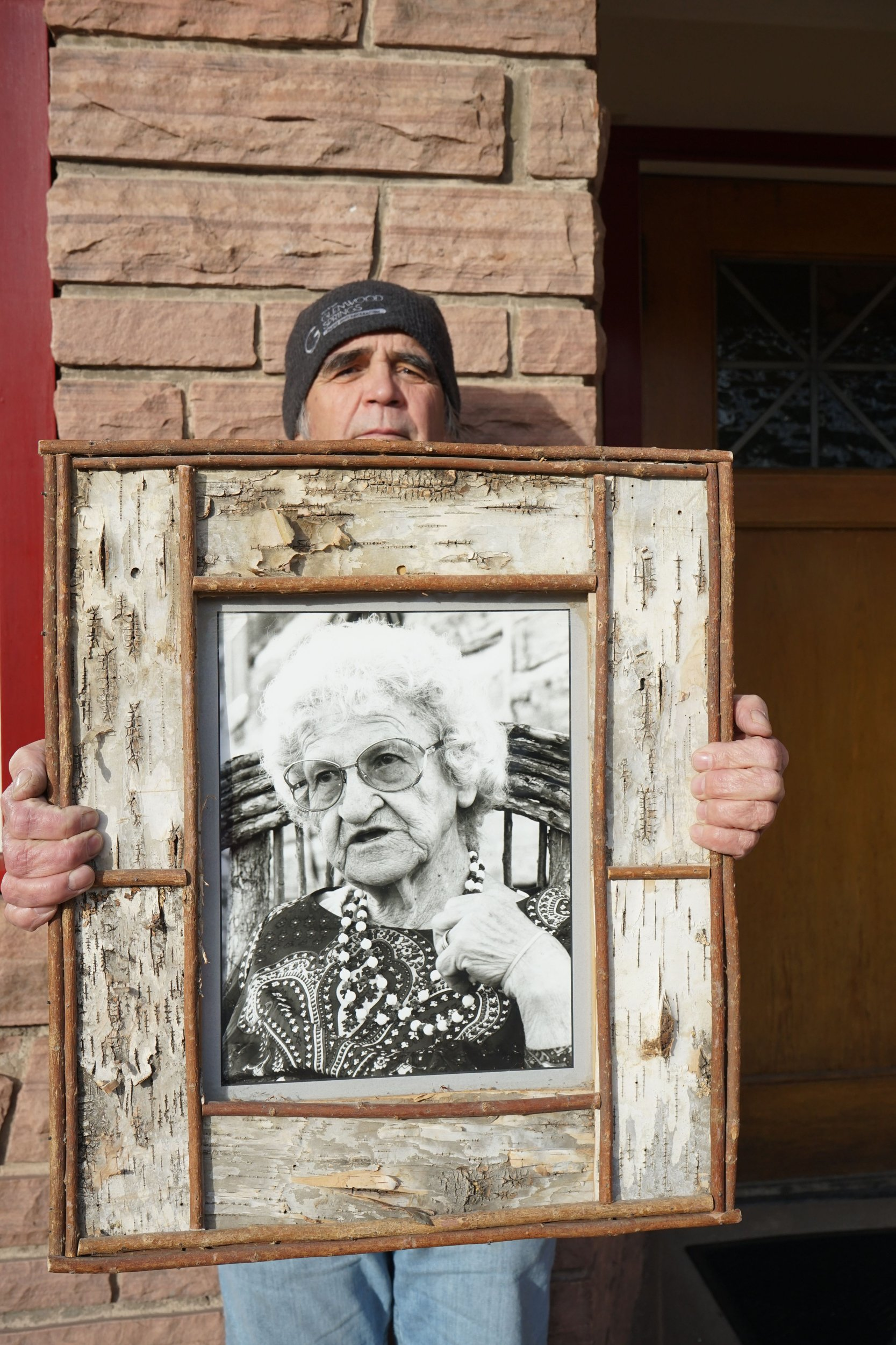 "Gerry Johnston holds a framed photo of Mary Ferguson outside the Dinkel Building, a former studio and office of KDNK, where he engineered Ferguson's show ""This I Remember"" in the 1980s and 1990s. Photo by Trina Ortega."