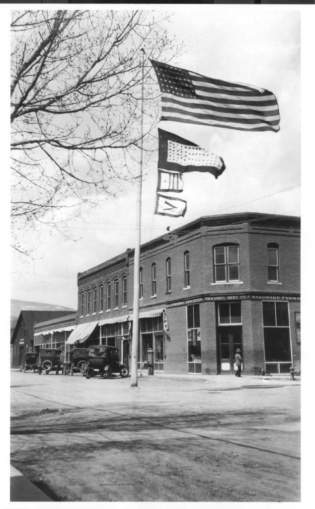 A dog sits in front of W.M. Dinkel Mercantile (The Black Nugget today) sometime around the end of WWI. The second flag from the top has a star for every local that served in the war. The lower flags are Liberty Loan Flags, awarded when a business or municipality surpassed its quota for selling bonds to finance the war. Image courtesy of Carbondale Historical Society and refined by Frank Norwood of Main St. Gallery and Framer.