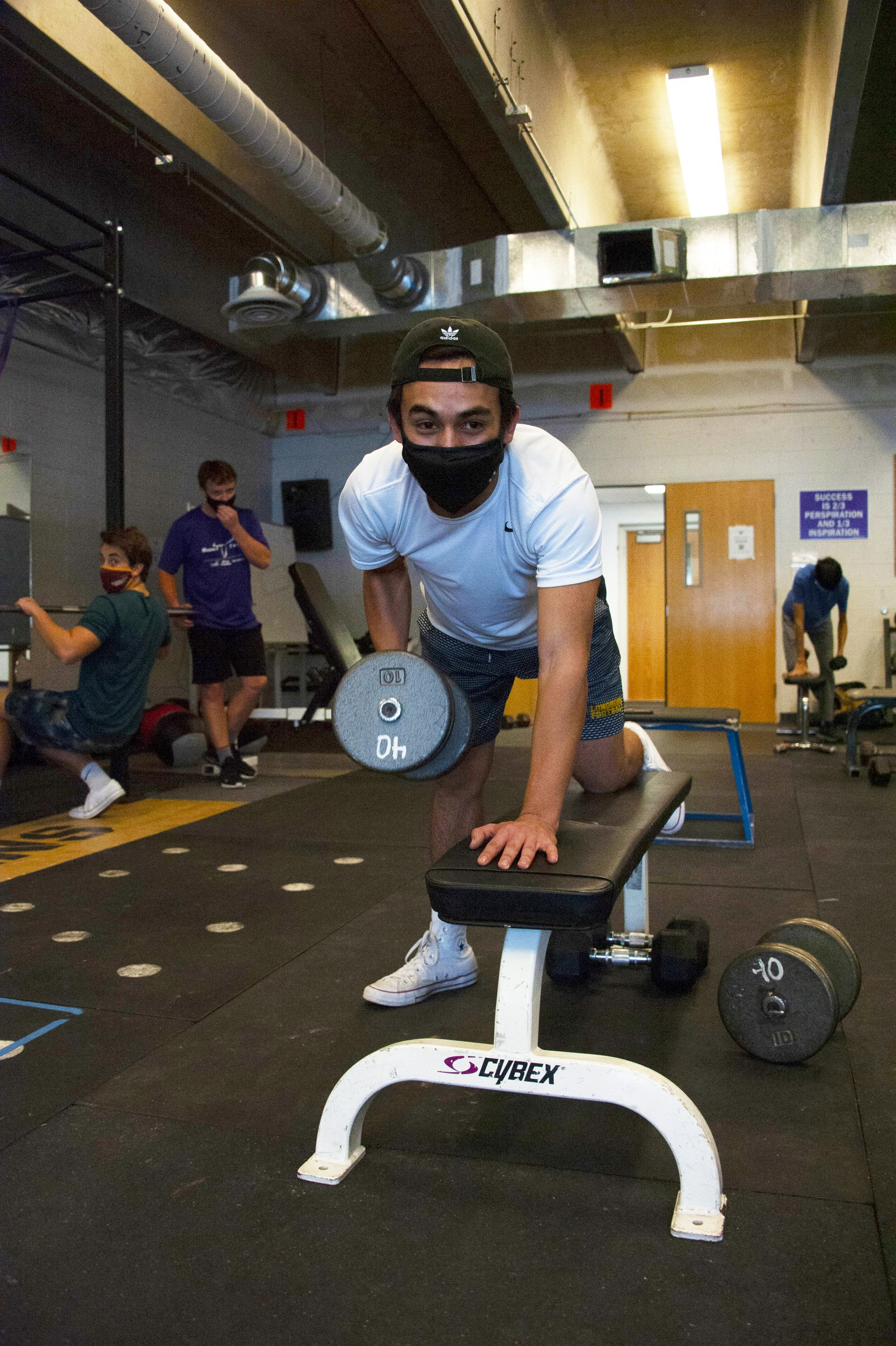 Senior Rulbe Alvarado, who made the all-state team as a Longhorns varsity junior, lifts at the gym as team members watch: junior Sam Sherry, wide receiver and linebacker, and sophomore Trevin Beckman, running back and linebacker. Photo by Roberta McGowan.