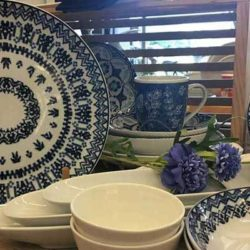 Blue & Cream designed serving bowl along with cream colored serving pieces of different sizes on display.