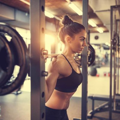 Stock image of woman getting ready to squat in a rack