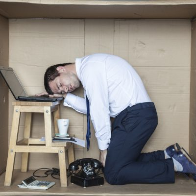Man in cardboard box with head on laptop