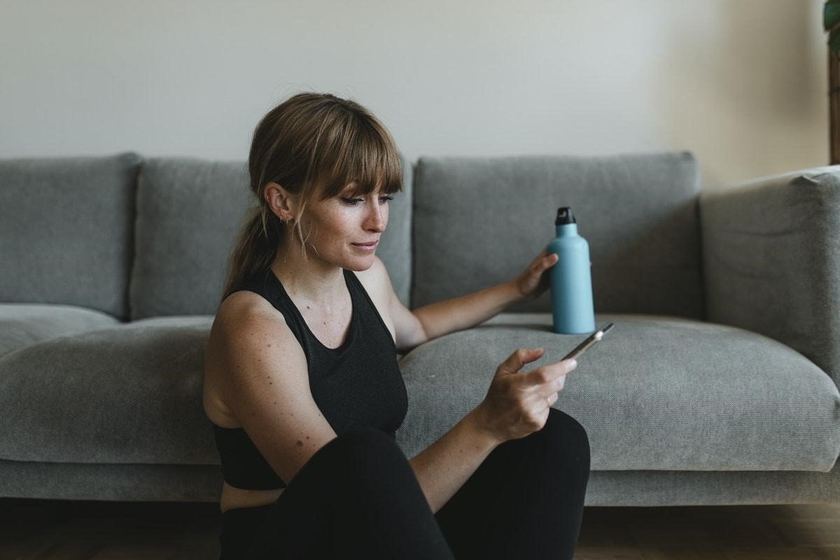 Woman looking at her phone post-workout
