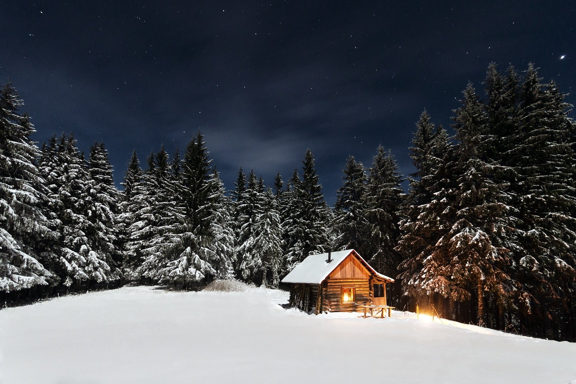 A log cabin at night in the wintertime, surrounded by snow