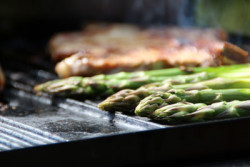 Close-up image of asparagus cooking on a grill.