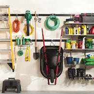 Image of outdoor tools hanging on a garage wall.